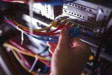 Close-Up of technician plugging patch cable in a rack mounted server i
